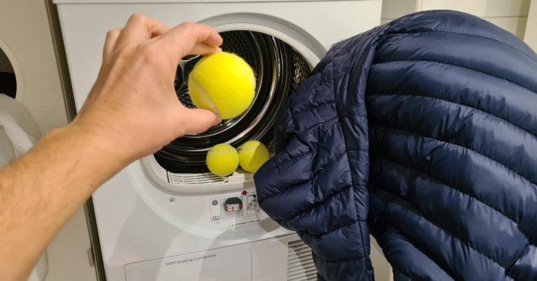 Hand lägger in tre tennisbollar och dunjacka i torktumlare